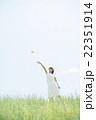 草原で紙飛行機を飛ばす女性 22351914