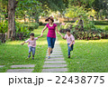 mother running in the park with sons 22438775