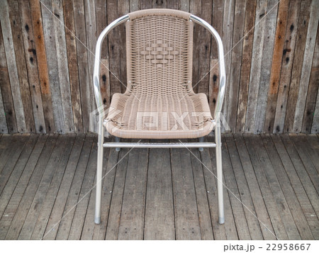 Metal chair with woven seat on old wooden floor 22958667