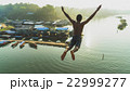 Young boy jumping into river 22999277