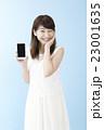 スマホを片手に笑顔の女性ブルーバック       23001635
