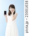 スマホを片手に笑顔の女性ブルーバック      23001638