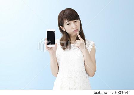 スマホを片手に笑顔の女性ブルーバック           23001649