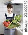 キッチンで沢山の野菜を持つ笑顔の女性    23100070