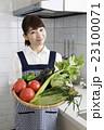 キッチンで沢山の野菜を持つ笑顔の女性    23100071