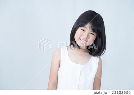 首を傾げて微笑む女の子 23102630