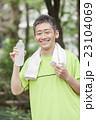 ジョギング後に水分補給する中年男性 23104069