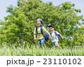 新緑の公園を走る小学生たち 23110102