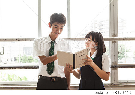 休み時間にノートを見せ合う男女生徒 23123419