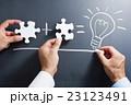 パズルのピースを組み合わせる手と黒板に点灯する電球を描く手 23123491
