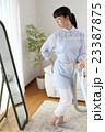 掃除をしながら体型の衰えに悩む主婦 23387875