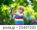 little kid boy shooting wooden slingshot 23407202