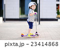 Toddler boy learning to ride scooter 23414868