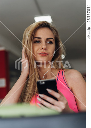 Blonde with a phone  at the gym. Listening to 23577854