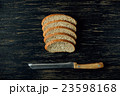Sliced bread and knife on black wooden table 23598168