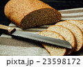 Sliced bread and knife on linen cloth, black table 23598172