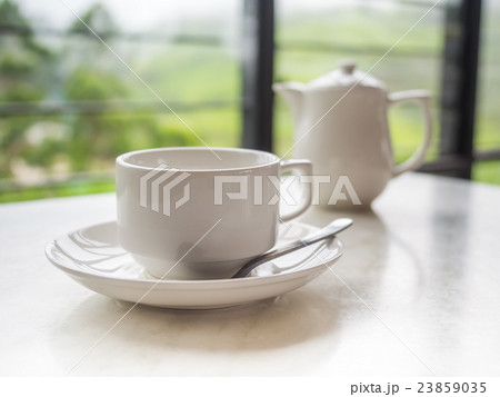 White teapot and tea cup on the table 23859035