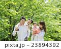 新緑の公園を歩く4人家族 23894392