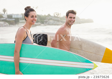 Couple with surfboard running on the beach 23975626
