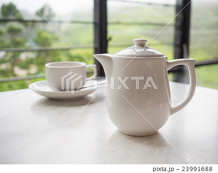White teapot and tea cup on the table 23991688
