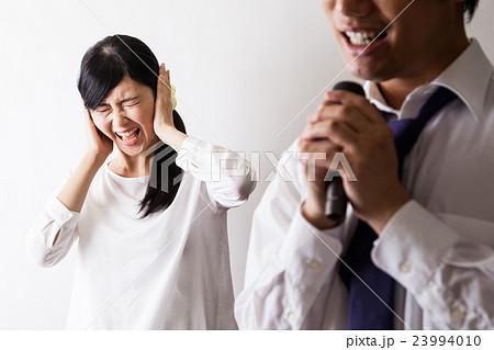 カラオケで歌う男と耳を塞ぐ女  23994010
