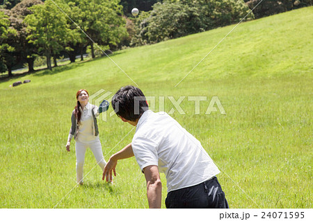 公園でキャッチボールをする男女 24071595