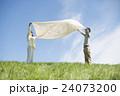 草原で布を広げるカップル 24073200