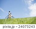 草原で自転車を押すカップル 24073243