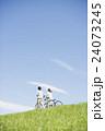 草原で自転車を押すカップル 24073245