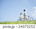 草原で自転車を押すカップル 24073252