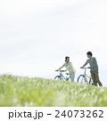 草原で自転車を押すカップル 24073262