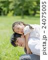 新緑の公園で遊ぶ父親と娘 24075005