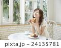ドーナッツを美味しそうに食べる若い女性 24135781
