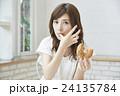 ドーナッツを食べる若い女性 24135784