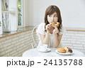 ドーナッツを食べる若い女性 24135788