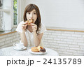 ドーナッツを食べる若い女性 24135789