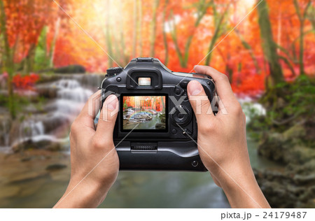 Hands holding the camera which taking photo of Beautiful waterfall with soft focus and rainbow in the forest 24179487
