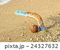 Boomerang and coconut on sandy beach near sea surf 24327632