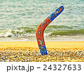Colorful boomerang on sandy beach against sea surf 24327633
