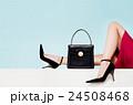 黒いハンドバッグとハイヒールの女性の足。 24508468