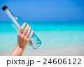 Bottle with a message in the hand background blue 24606122