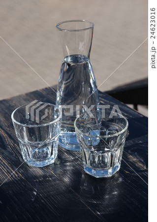 Two glasses and a water-bottle on a black wooden table of a cafeの写真素材 [24623016] - PIXTA