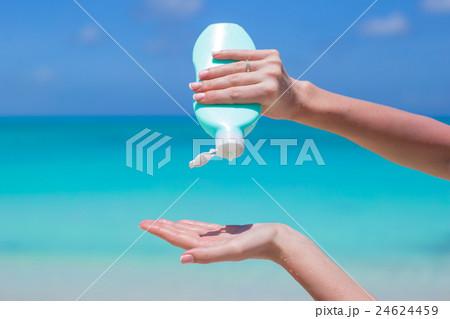 Woman hands putting sunscreen from a suncream 24624459