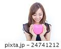 ピンク色のハートを持つ若い女性 目線外し 24741212