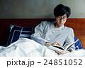ベッドで本を読む男性 24851052