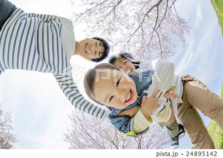 桜の咲く公園で遊ぶ3人家族 24895142