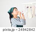 室内干しした洗濯物の匂いを嗅ぐ女性 24942842