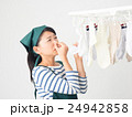 室内干しした洗濯物の匂いを嗅ぐ女性 24942858