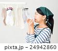 室内干しした洗濯物の匂いを嗅ぐ女性 24942860