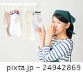 室内干しした洗濯物の匂いを嗅ぐ女性 24942869